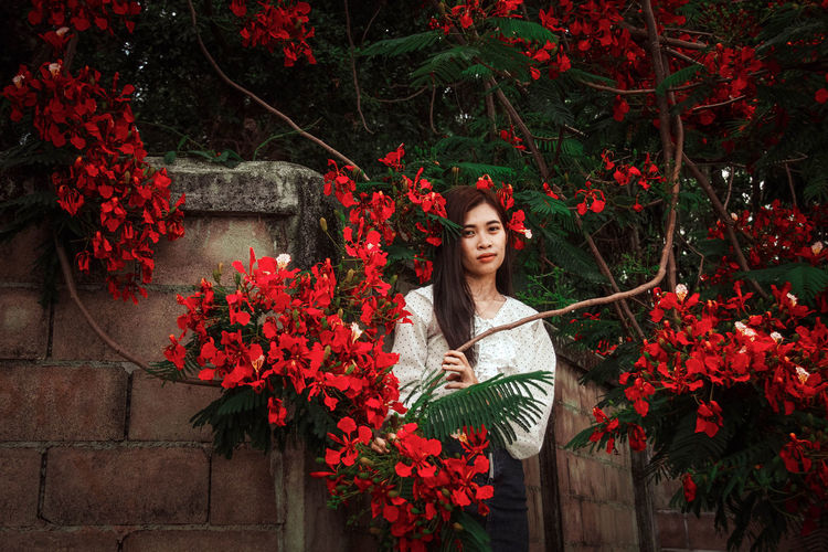 Portrait of young woman standing by red flowering plants