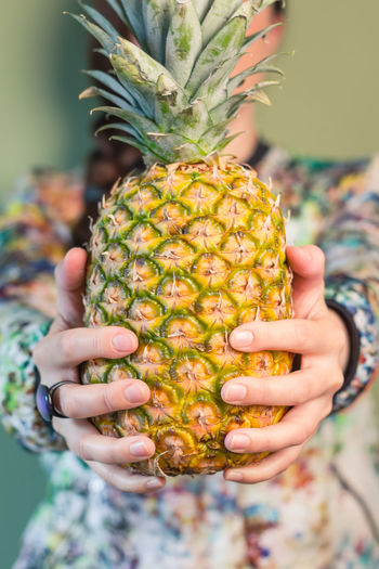 Midsection of woman holding pineapple against green background