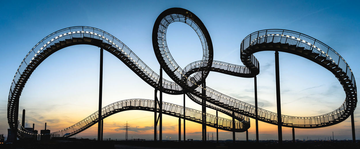 Low Angle View Of Illuminated Rollercoaster Against Sky During Sunset