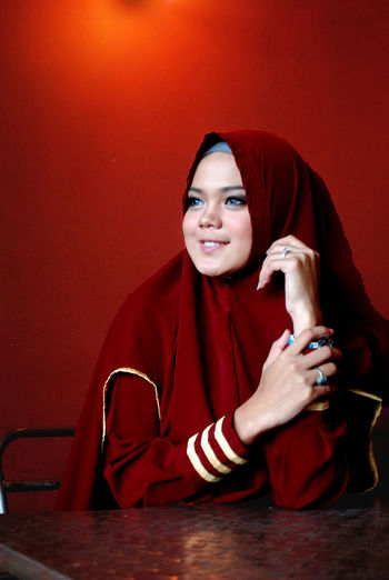 Smiling young woman in hijab looking away while sitting against red wall