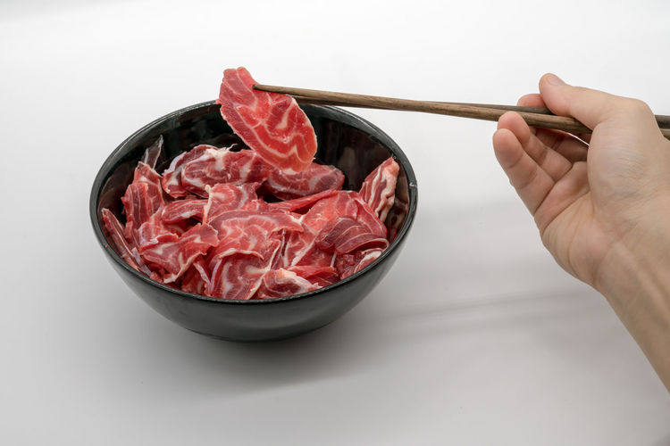 Close-up of hand holding meat with chopsticks in bowl on table
