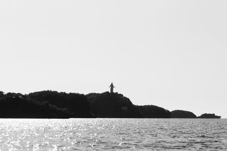 Silhouette man by sea against clear sky