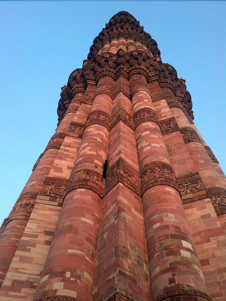 Qutb Minar at 73 metres, is world's tallest rubble masonry minaret. Qutb Minar, along with the ancient and medieval monuments surrounding it, form the Qutb Complex, which is a UNESCO World Heritage site. The tall minaret was constructed in 1192 by Qutab-ud-din Aibak, and later completed by his successor Iltutmish. The soaring conical tower is an exquisite example of Indo-Islamic Afghan architecture. 73meters Delhi India QutubMinar Red UNESCO World Heritage Site Architecture Built Structure Delhimonuments History Incredible India Low Angle View Minaret Mobilephotography Monument Motox Nofilter Sandstone Structure Tallest Brick Minaret Tallest Building Tourism Tower Of Victory Travel Travel Destinations