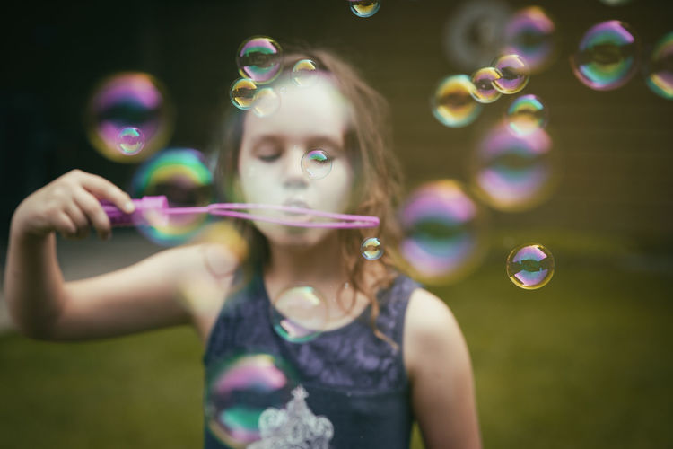 Girl Blowing Bubbles While Playing At Public Park