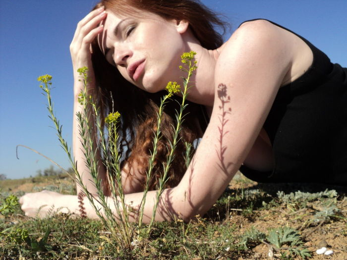 Woman With Brown Hair Sitting On Field During Sunny Day