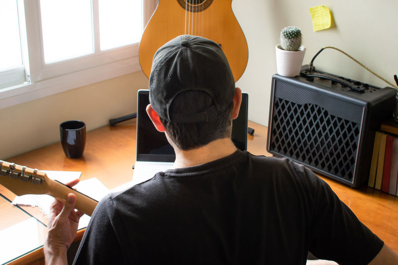 Rear view of man playing guitar while using laptop at home