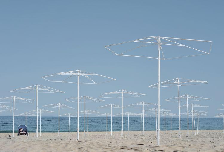 Empty Umbrellas On Beach Against Clear Sky