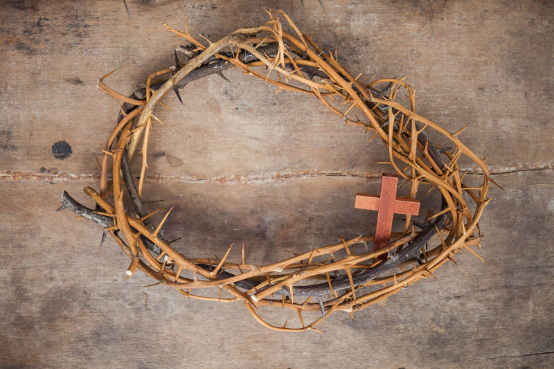 Directly above shot of thorn wreath with cross on wooden table