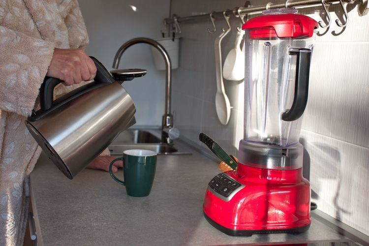 Indoors  Household Equipment One Person Holding Red Human Body Part Equipment Metal Container Human Hand Preparation  Occupation Real People Food And Drink Heat - Temperature Kitchen Woman Tea Cup Pouring Sink Blender Natural Light Bathrobe Midsection