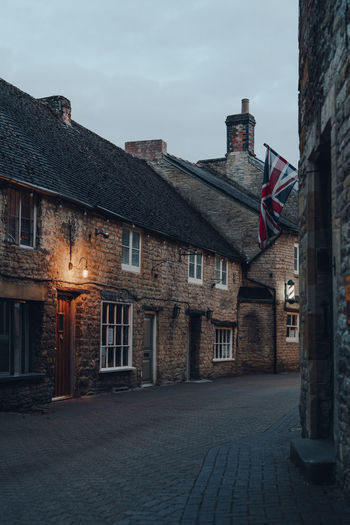 Limestone cottages on a narrow street in stow-on-the-wold, cotswolds, uk, in the evening.