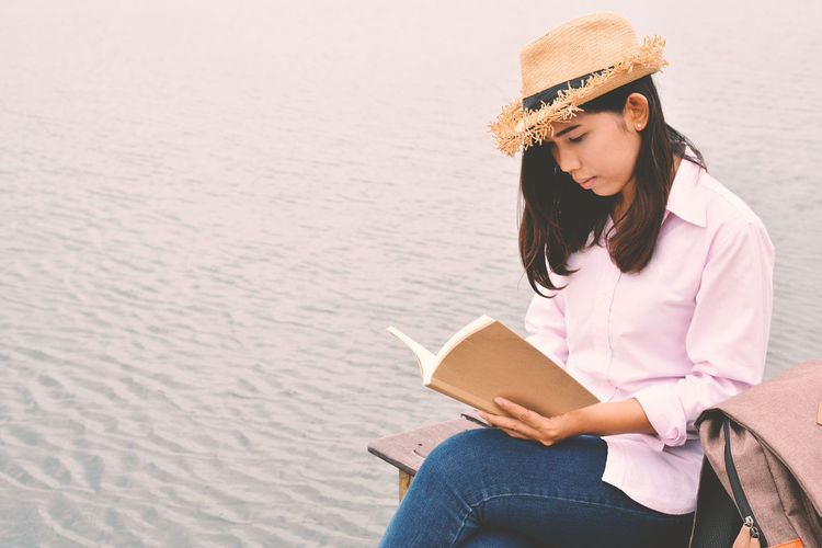 Young woman reading book at beach