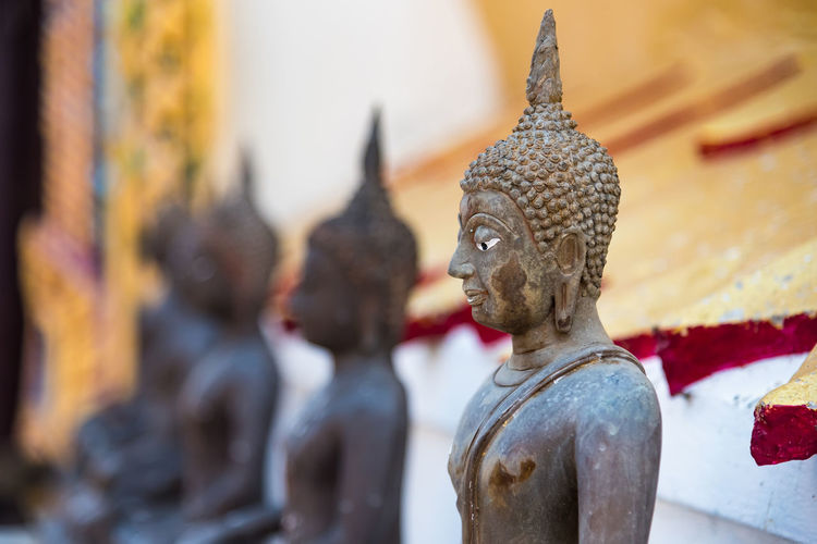 Close-up of buddha statues outside temple