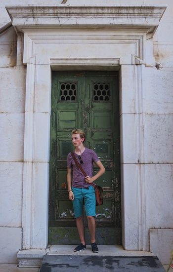 Full length of young man standing by closed green doors
