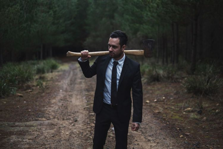 Young Businessman With Axe Standing On Dirt Road In Forest