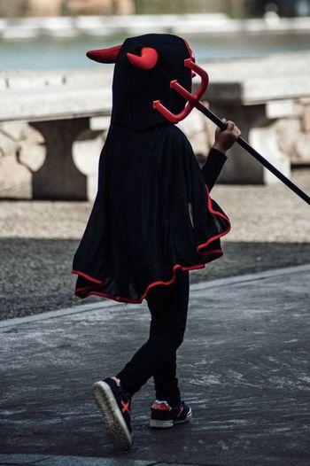 Person walking in devil costume on footpath