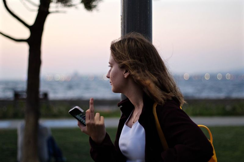 Woman using mobile phone in city against sky