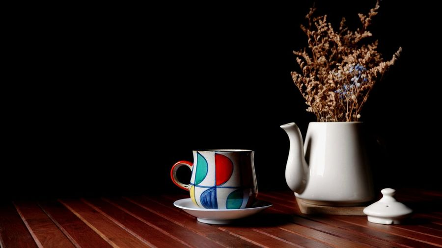 Ceramic coffee cup with gypsophila dry flowers in teapot on wooden table with black background in vintage style, hot coffee decorations concept Ceramics Container Space Still Life Black Background Multicolored Arrangements Pattern Procelien Wooden Planks Decorations Vintage Gypsophila Dry Flowers EyeEm Selects Black Background Table Close-up Saucer Vase Coffee Cup Tea Coffee - Drink Coffee Beverage