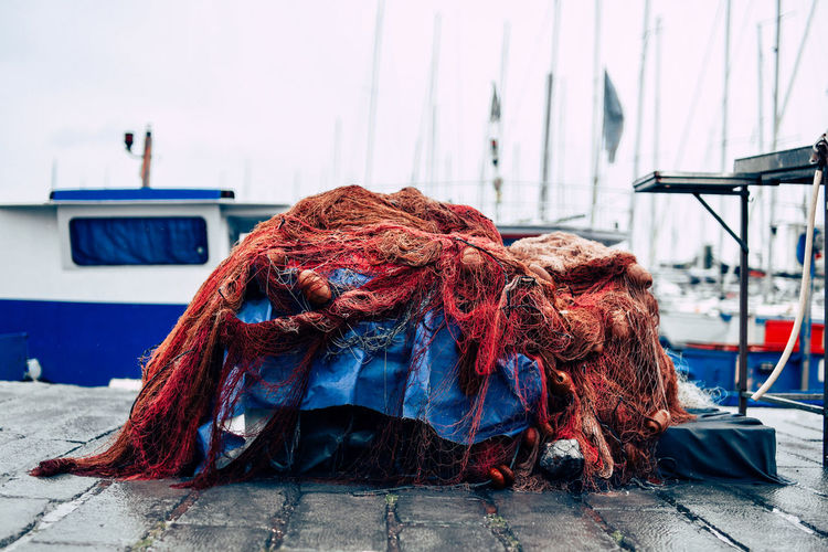 Tangled fishing net on footpath at harbor