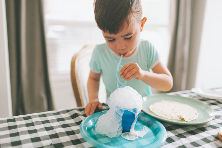 Boy playing with milk while sitting on table at home