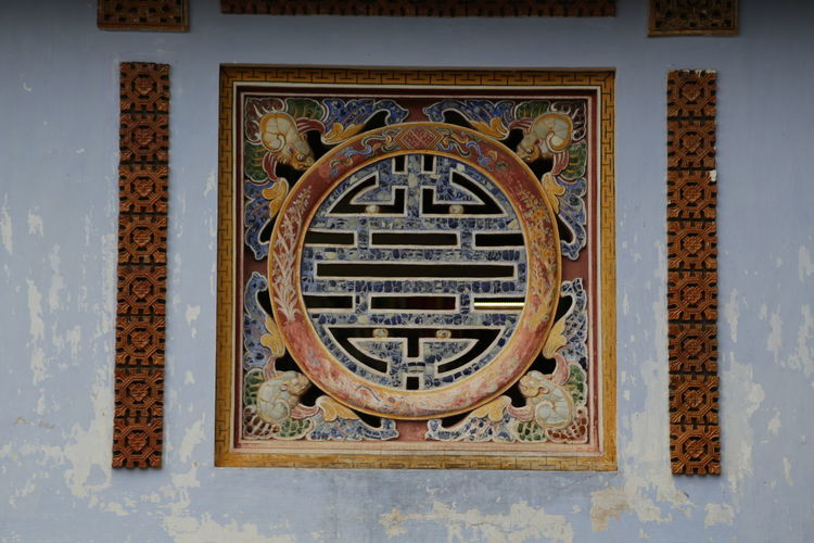 Close-up of ornate window on wall of building