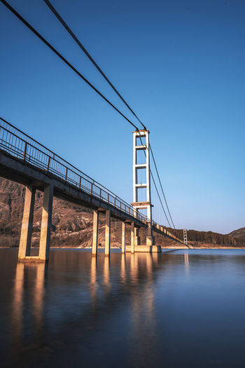 The longest suspension bridge in Bulgaria over Studen Kladenez dam with distance between the two towers of 260m. The only way to reach Lisicite village Reflection Water Sunset Nature Sky Bridge Travel Tower Lake Mountain Direction Pylon Way Suspension Dam Bulgaria Metal Overcast Wooden Suspension Bridge Longest Warm Clothing Bridge - Man Made Structure Built Structure Connection Architecture Clear Sky River Engineering Transportation Blue Waterfront Day Copy Space Low Angle View Outdoors