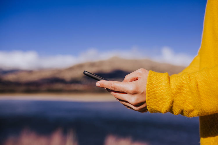 Cropped image of woman using phone outdoors