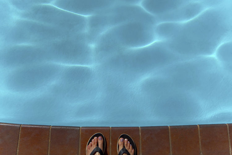 Low section of person standing on swimming pool