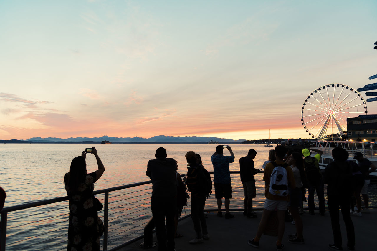 Silhouetted people on the Seattle waterfront with smart phones taking photos of vibrant sunset and ferris wheel lit at dusk. Elliott Bay Ferris Wheel Ferry Industry Pacific Puget Sound Salish Sea Seattle Silhouette Transportation Travel Boat Day Nature Outdoors Sailing Scenics Sea Shipping  Sky Smart Phone Sunset Tourism Water Waterfront Summer Exploratorium