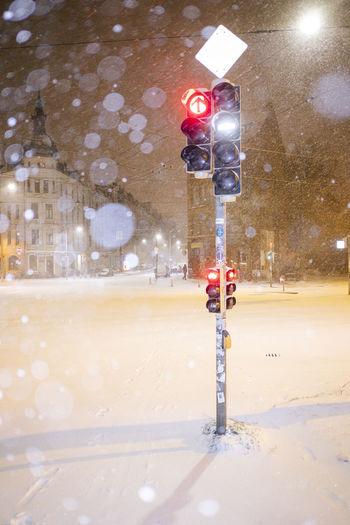 Illuminated street light in city at night during winter