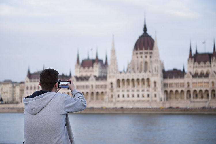 Tourist young man taking a photo with his cell to the Hungarian parliament from the other side of the Danube river Activity Architecture Building Exterior Built Structure City Holding One Person Outdoors Photographing Photography Themes Portable Information Device Real People Sky Standing Technology Tourism Travel Travel Destinations Water Wireless Technology