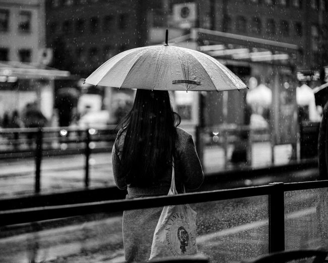 Rear view of woman standing on railing during rainy season