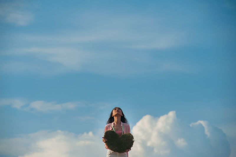 Woman holding heart shape while looking up against sky