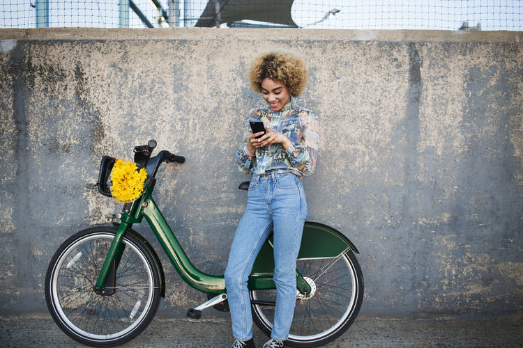 Woman using phone while standing by bicycle against wall