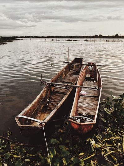 Abandoned Boat Moored In Lake Against Sky