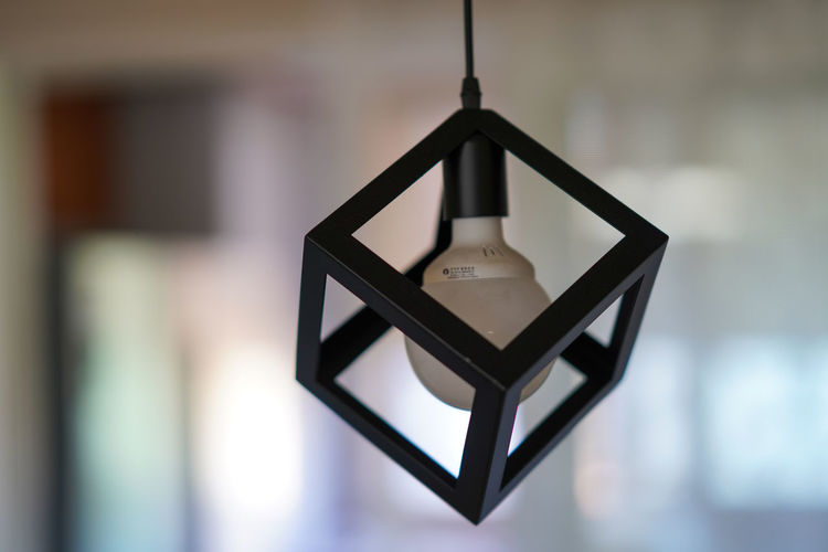 Close-up of electric lamp hanging against wall at home