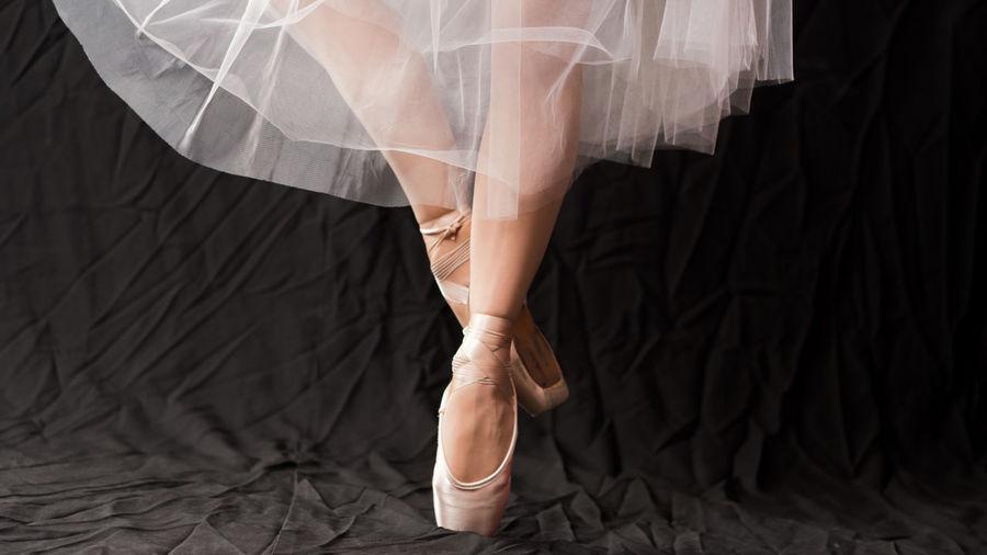 Low section of female ballet dancer dancing against black backdrop
