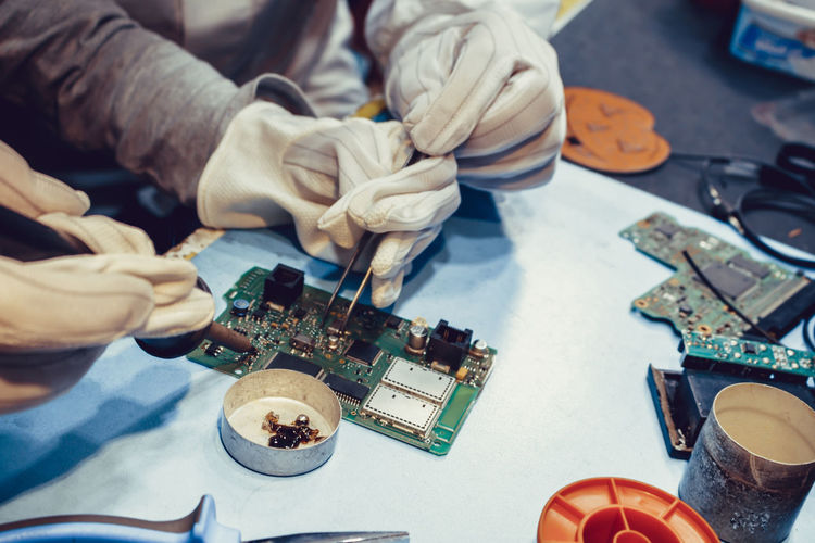 Cropped image of technicians repairing circuit board on table indoors