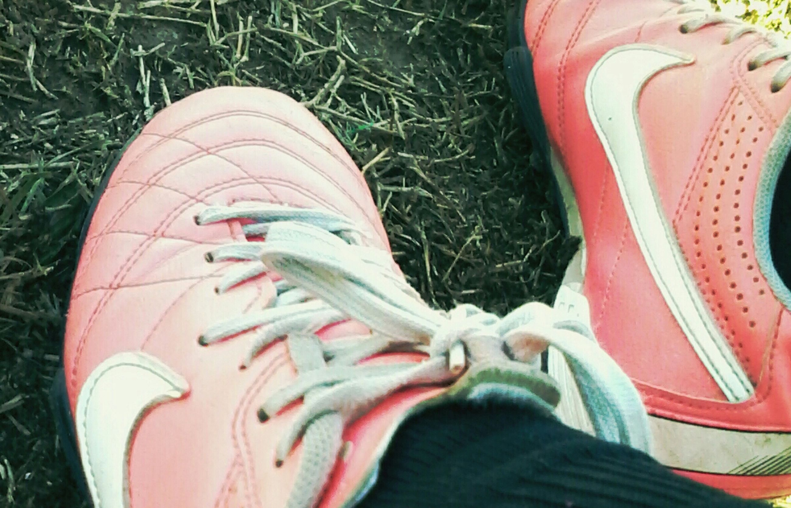 low section, shoe, person, high angle view, personal perspective, footwear, human foot, lifestyles, field, pair, grass, standing, leisure activity, part of, canvas shoe, unrecognizable person, jeans