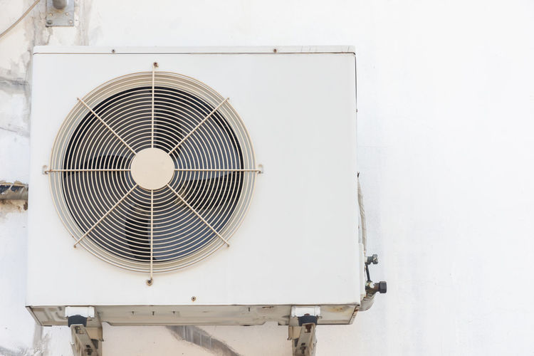 Close-up of electric fan against white wall