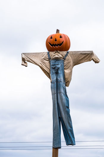 Low angle view of scarecrow against sky