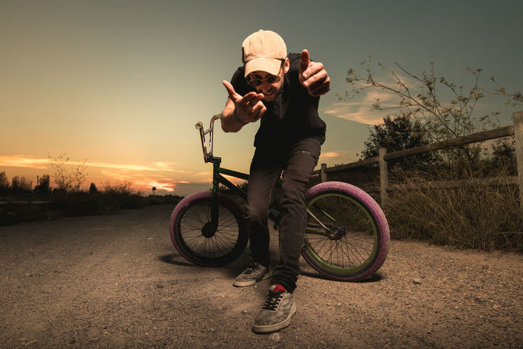 Man riding bicycle on street against sky during sunset