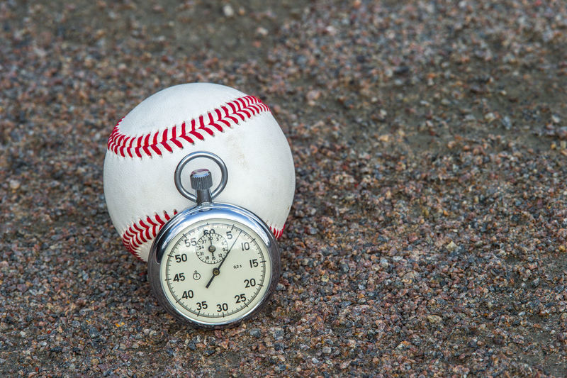 Close-up of ball and stopwatch on the ground