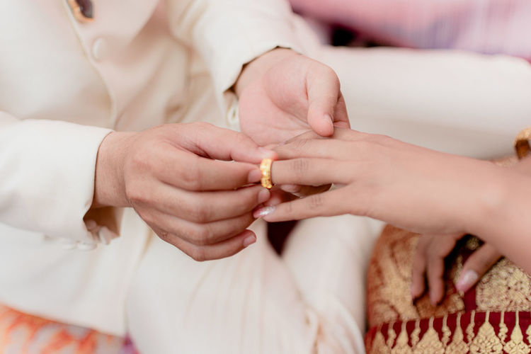 Midsection of bridegroom wearing ring to bride in wedding ceremony