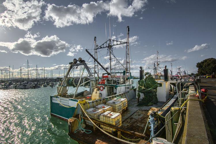 Fishing trawlers moored at harbor in sea against sky
