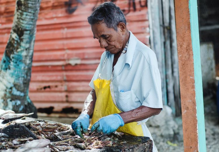 Man cleaning fishes at market