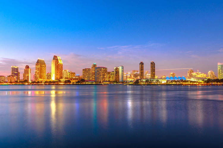 Panoramic landscape of San Diego skyline with illuminated skyscrapers reflecting in San Diego Bay at twilight. Districts of Waterfront Marina skyline and urban downtown cityscape at sunset light. Coronado Coronado Beach Coronado Island Sea Beach San Diego California United States America American Skyline Seascape Cityscape Sun Dock Port Holiday Vacations Sunset Night Panorama View Pier Architecture Built Structure Building Exterior Sky Urban Skyline Building Water Skyscraper City Landscape Office Building Exterior Reflection Waterfront Travel Destinations No People Nature Tall - High Tower Modern Outdoors Financial District