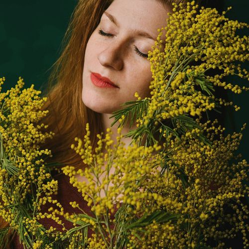 Close-Up Of Young Woman With Yellow Flowers