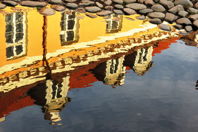 Reflection of building in puddle on cobbled street