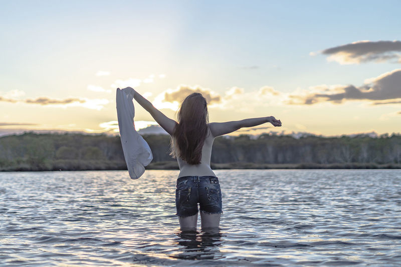 Adult Arms Raised Beauty In Nature Hairstyle Human Arm Leisure Activity Lifestyles Limb Nature One Person Outdoors Real People Rear View Scenics - Nature Sky Standing Sunset Three Quarter Length Water Waterfront Women Young Adult