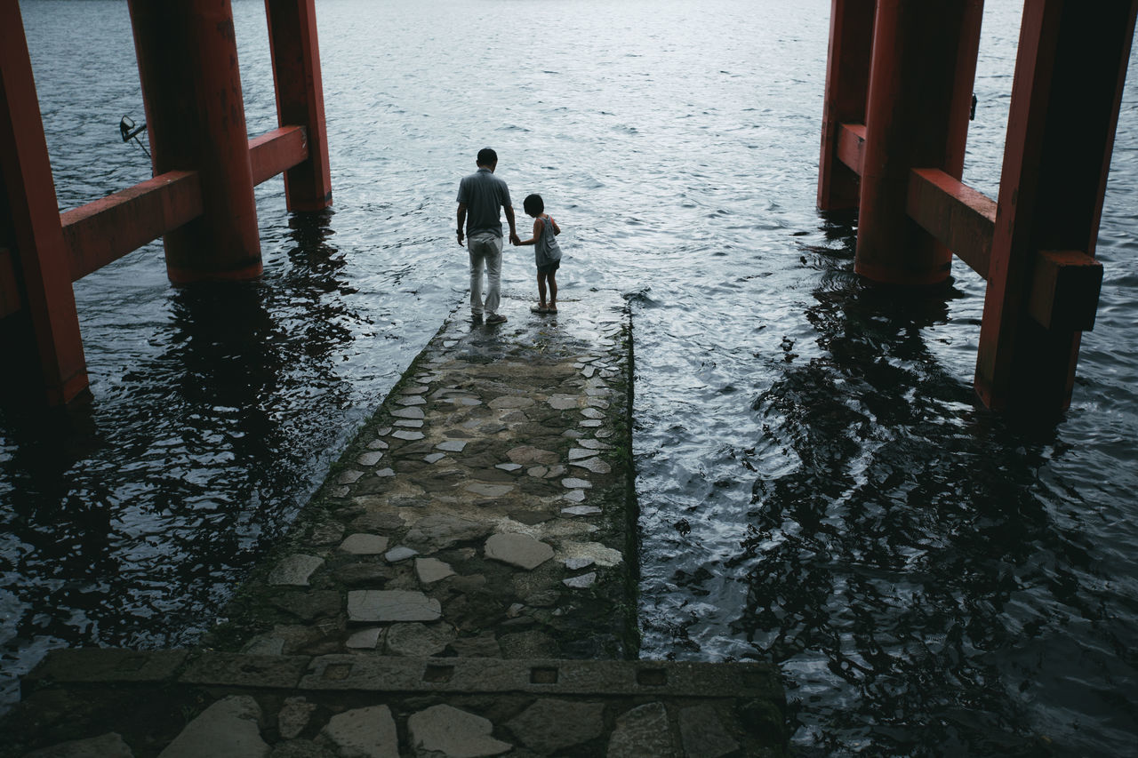 Father and daughter standing on jetty at sea